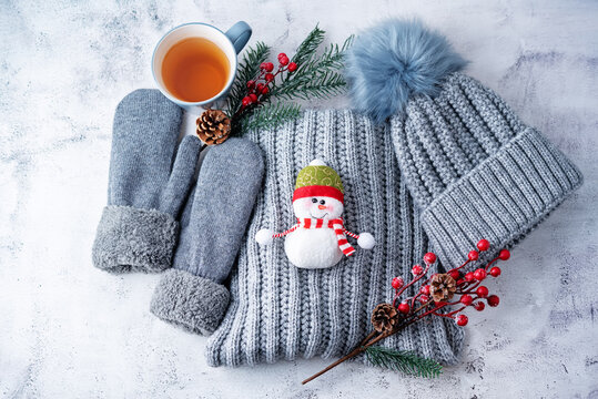 Winter Christmas holidays background with Cup of tea and wool hat, mittens and scarf