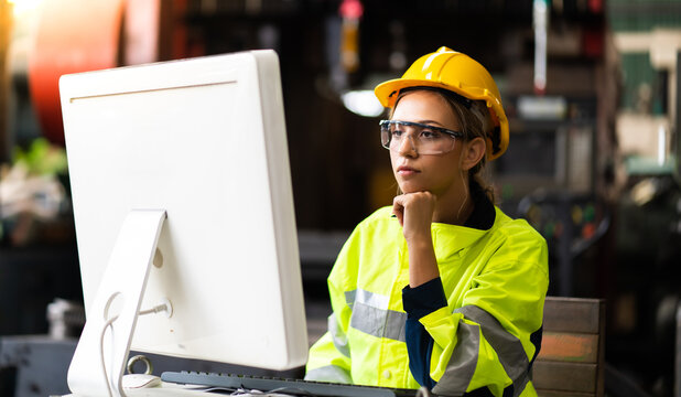 Female Quality control inspector checking workers at factory. Woman engineer with yellow hard hat helmet working on desktop computer inside factory