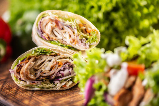 Tortilla wraps with meat, vegetables, mayonnaise with a salad on the side