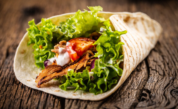 Tortilla with meat, tomato, salad, onion and cream