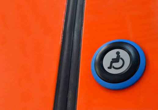 Button with sign wheelchair.  Train door push button press to open sliding mechanical door at a train station platform. Special express train for disabled people.