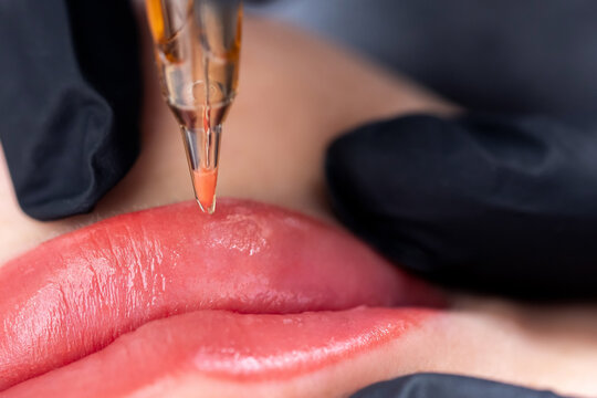Macro photo of process of applying permanent makeup tattoo of red on lips woman