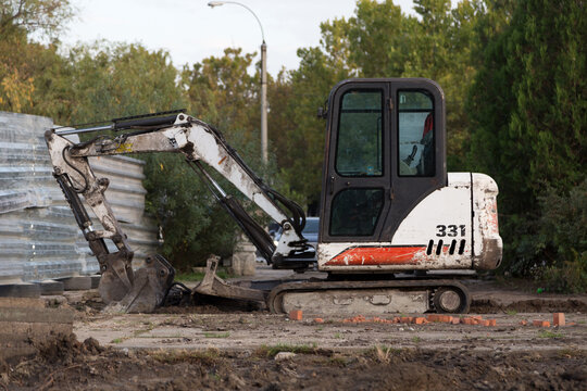 The excavator digs the ground in the park.