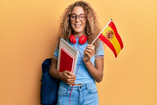 Beautiful caucasian teenager girl exchange student holding spanish flag winking looking at the camera with sexy expression, cheerful and happy face.