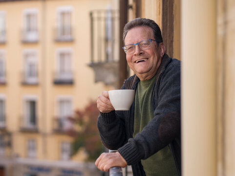 lifestyle portrait of happy and cheerful mature man 65 to 70 years old at home balcony feeling positive and relaxed drinking coffee enjoying retirement smiling to the street view