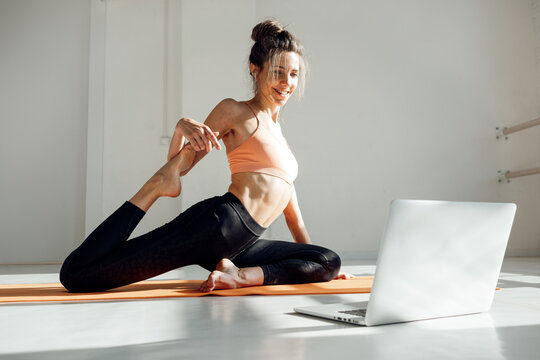 Yoga woman instructor taking online lesson using video call in laptop.. Fitness woman practicing yoga with trainer using  video conference
