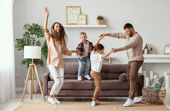 happy family mother father and children dancing at home