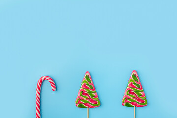 Christmas candies on blue background. Candy shapes, candy cane. Flat lay, top view. Copy space