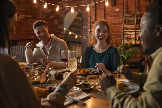 Group of cheerful adult people sitting at dinner table while enjoying party with outdoor lighting