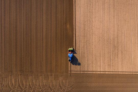 Vogelperspektive auf einen Traktor beim Umpflügen eines Ackers hinterläßt Spuren auf dem Feld