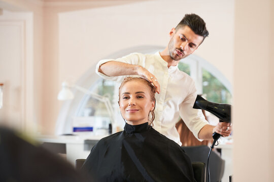Hairdresser drying and straightening hair