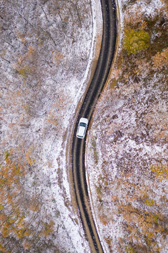 Aerial view of car in a countryside road with snow in winter - White car driving through the wood on a winter day in Italy - Travel and seasonal concepts