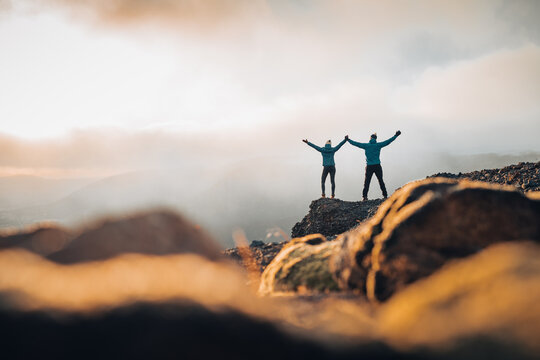 Couple travelers Man and Woman standing on cliff relaxing mountains and clouds aerial view Love and Travel happy emotions Lifestyle concept. Young family traveling active adventure vacations