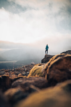 Solo traveler Woman standing on cliff relaxing mountains and clouds aerial view Love and Travel happy emotions Lifestyle concept. Young female traveling active adventure vacations. Landscape Iceland