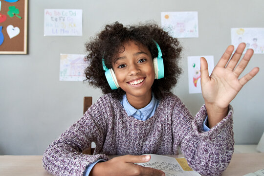 Happy african american kid child girl wearing headphones waving hand talking with remote teacher on social distance learning video conference call chat class, headshot zoom portrait, web cam view.
