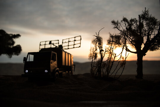 Silhouette of mobile air defence truck with radar antenna during sunset. Satellite dishes or radio antennas against evening sky.