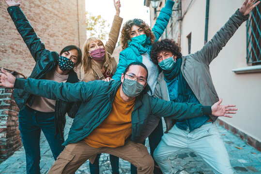 Happy friends walking on city street - New normal concept with young people having fun together covered by face masks