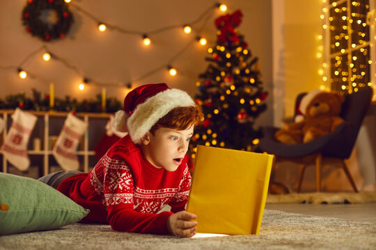 Little boy opens magic book and reads wonderful stories and fairy tales on Christmas Eve at home