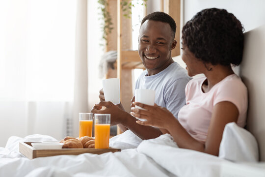 Happy young black couple eating breakfast in bed in morning