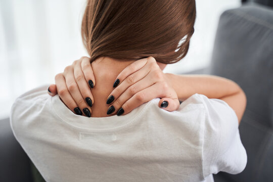 Tired young woman touching stiff neck