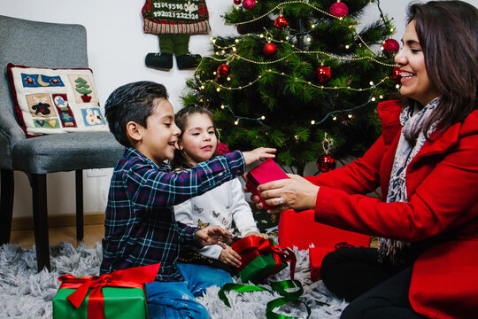 Latin children opening Christmas present. Hispanic mother giving gift to his son
