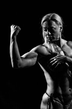muscular female against black background