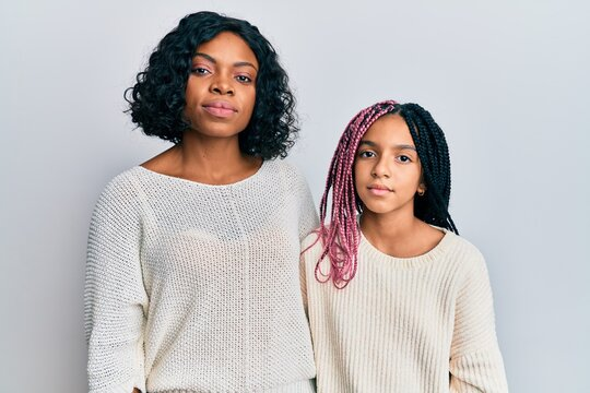 Beautiful african american mother and daughter wearing casual clothes and hugging relaxed with serious expression on face. simple and natural looking at the camera.