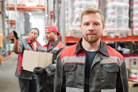 Successful young bearded man in workwear looking at you against colleagues