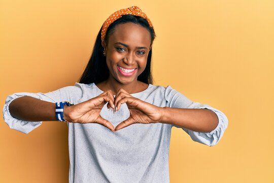Young african woman wearing casual clothes over yellow background smiling in love showing heart symbol and shape with hands. romantic concept.