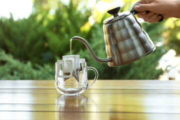 Woman pouring hot water into glass cup with drip coffee bag from kettle at wooden table, closeup