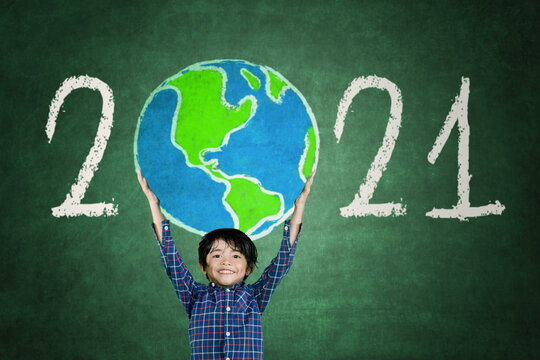 Little boy lifting a globe drawn with number 2021
