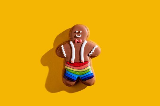 Lgbt pride. Yellow conceptual background. Diversity tolerance. Individuality freedom. Happy African gay gingerbread man in rainbow shorts isolated on bright orange copy space.