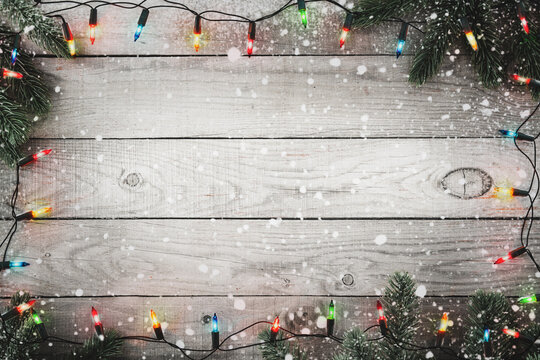 Christmas background - Christmas lights bulb and fir branch and snowflake on rustic wood table, frame border design. Merry Christmas and New Year holiday background. top view.