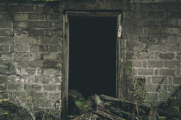 Part of an old brick house with wooden door frame. Abandoned building interior. Darkness horror and...