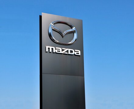 Udine, Italy. October 14, 2020. Mazda logo outside the dealership of the area, against blue sky.  It is the symbol of the   japanese vehicle manufacturer