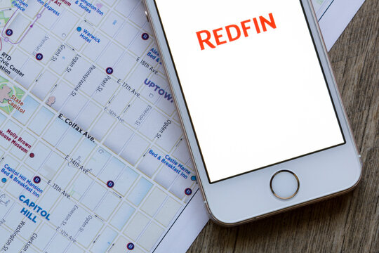 Portland, OR, USA - Apr 8, 2020: Redfin mobile app welcome page is seen on a smartphone against city map background. Redfin is a real estate brokerage company based in Seattle, Washington.