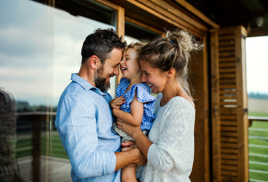 Family with small daughter standing on patio of wooden cabin, holiday in nature concept.
