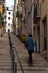 man climbs some stairs with a bouquet of flowers