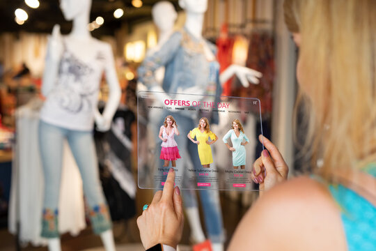 Woman using futuristic technology while shopping for new clothes in store