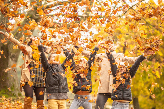 Family fun outdoors in the autumn by throwing fallen leaves up in the air
