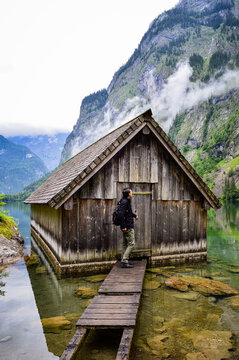 Vertical shot of a man opening a door of a wooden boathouse in Berchtesgaden National Park, Germany