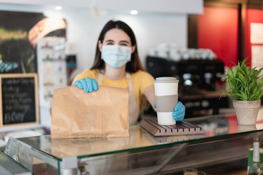 Young woman serving takeaway coffee and breakfast at bakery shop while wearing protective face mask - Delivery service for Coronavirus outbreak concept - Focus on right hand
