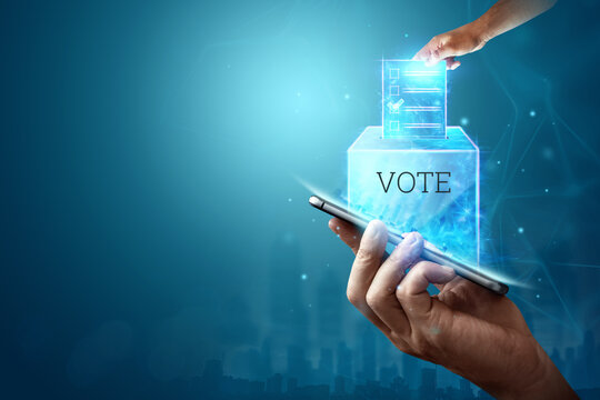Online voting, Hand with a hologram ballot and a box for Internet voting in a mobile phone on a blue background. Mixed environment, e-voting technology concept.