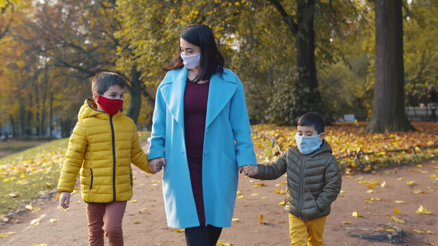 Mother and two little children in face mask walking in autumn park