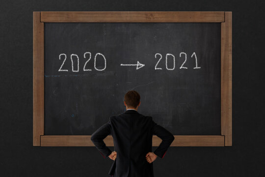 business 2021 concept, business man look on the black board that change from year 2020 to new year 2021 , copy space