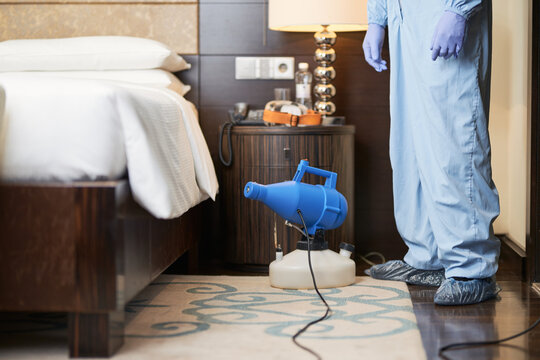 Man in protective clothing disinfecting the bedroom