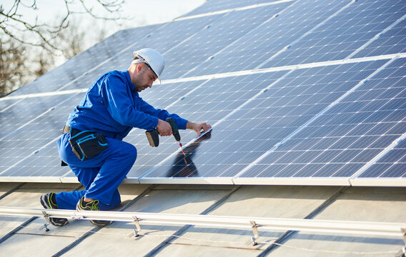 Male worker in blue suit and protective helmet installing solar photovoltaic panel system using screwdriver. Professional electrician mounting blue solar module on roof of modern house.