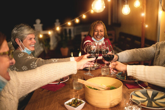 Multiracial senior people celebrate new year's eve together doing dinner outdoor while wearing face mask for coronavirus outbreak - Holidays concept - Soft focus on left hand