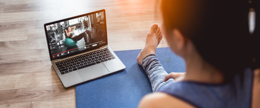Young sporty woman in sportswear is sitting on the floor and watching online tutorials,Fitness training online on laptop during covid-19 or coronavirus outbreak at home in the living room.