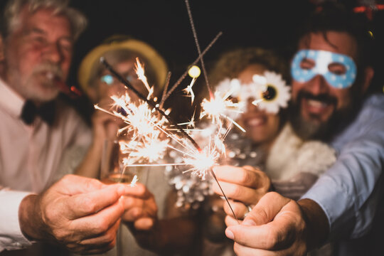 group of four people enjoying new year night celebrating with sparklers in the middle and looking at the camera - adults having fun together